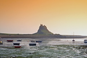 Lindisfarne_castle_at_sunset,_boats_at_low_tide